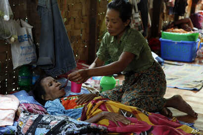 FILE - A family member takes care of a HIV patient at HIV/AIDS care center founded by Phyu Phyu Thin, a parliament member of Myanmar Opposition Leader Aung San Suu Kyi's National League for Democracy Party, in outskirts of Yangon, Myanmar.