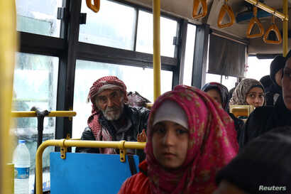 Evacuees from the Shi'ite Muslim villages of al-Foua and Kefraya ride a bus at insurgent-held al-Rashideen in the province of Aleppo, Dec. 22, 2016.