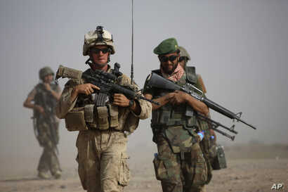A US Marine and an Afghan soldier are seen on joint patrol in Helmand province, southern Afghanistan (file photo).