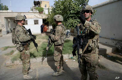 U.S. military forces stand guard during a visit by Kabul's officials in the governor's compound in Kandahar, Afghanistan, Aug. 4, 2016.