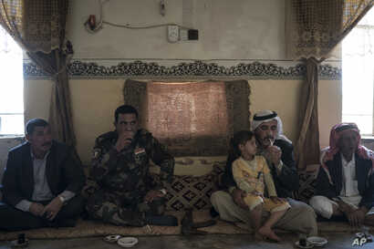 FILE - A local fighter and residents gather at the mayor's home in the Bijwaniya village, south of Mosul, Iraq, Nov. 12, 2017. Five young men were taken by unidentified gunmen after the village was liberated from Islamic State militants and despite m...