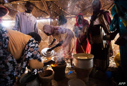 Women use fuel-efficient cook stoves make their meals in a food distribution center in the Rwanda camp for internally displaced people (IDP) in Tawila, North Darfur, March 4, 2014.
