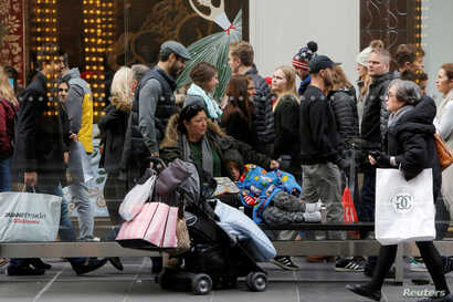 A woman sits at a bus stop with a child during Black Friday in Manhattan, New York, Nov. 25, 2016.
