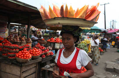 FILE - A woman sells skinned pawpaw, papaya, as she walks in a market on World Food Day in Lagos, Nigeria,  Oct. 16, 2012.