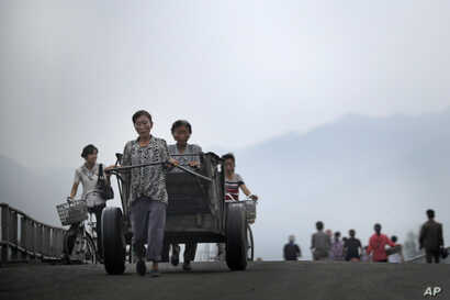 North Korean women push their cart and bicycles over a bridge in Hamhung, North Korea, July 21, 2017.
