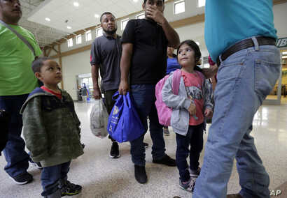 FILE - A group of immigrants from Honduras and Guatemala seeking asylum receive help the bus station after they were processed and released by U.S. Customs and Border Protection, June 21, 2018, in McAllen, Texas.