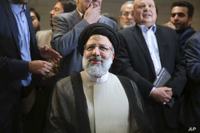 FILE- Iranian cleric Ebrahim Raisi registers his candidacy for the May 19 presidential elections at the Interior Ministry in Tehran, Iran, April 14, 2017. More than 1,600 people registered to run. Hopefuls only must believe in Iran's form of governme...
