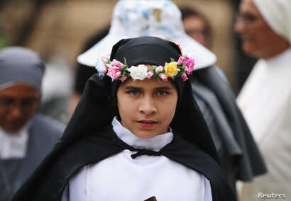 A young woman dressed as St. Rosa of Lima, patron saint of Peru, waits for Pope Francis to arrive at the nunciature, in Lima, Peru, Jan. 18, 2018.