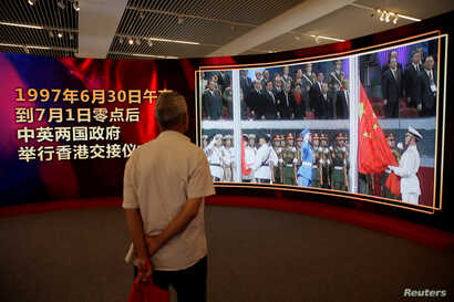 A visitor watches a video of the 1997 Hong Kong handover ceremony during an exhibition to celebrate the 20th anniversary of its handover to Chinese rule, at the National Museum of China in Beijing, June 27, 2017.