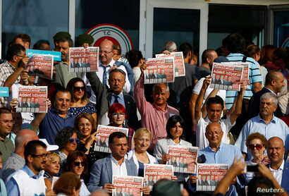 Lawmakers and press freedom activists hold copies of the Cumhuriyet newspaper during trial of 17 writers, executives and lawyers of the secularist Cumhuriyet newspaper in Silivri near Istanbul, Turkey, Sept. 11, 2017.