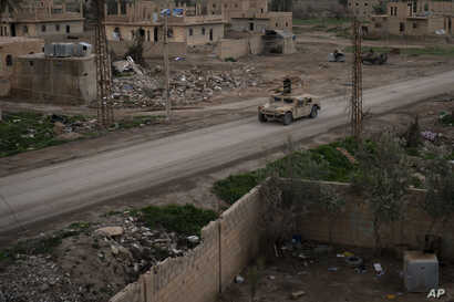 A Humvee drives in a village recently retaken from Islamic State militants by U.S.-backed Syrian Democratic Forces near Baghouz, Syria, Feb. 17, 2019.
