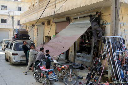 Residents work on fixing a damaged shop in the town of Darat Izza, province of Aleppo, Syria, Feb. 28, 2016.