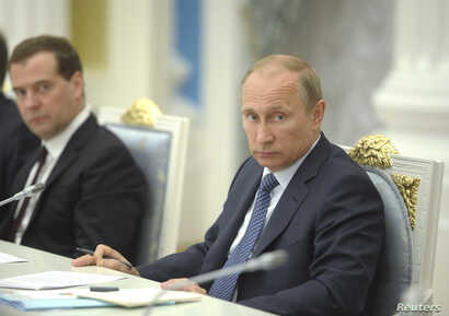 Russian President Vladimir Putin (R) chairs a meeting on economic and social issues, as Prime Minister Dmitry Medvedev sits nearby, in Moscow, May 7, 2014.