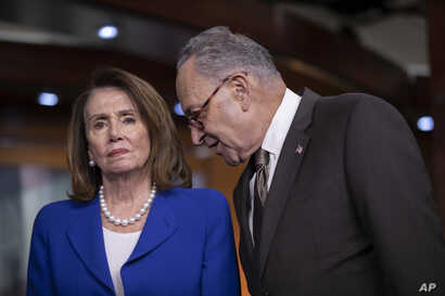 FILE - House Minority Leader Nancy Pelosi, D-Calif., left, and Senate Minority Leader Chuck Schumer, D-N.Y., confer as they call for action from President Donald Trump.
