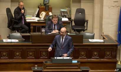 Belgian Prime Minister Charles Michel, center, addresses Belgium's parliament announcing security measures after the recent deadly Paris attacks, in Brussels, Nov. 19, 2015.