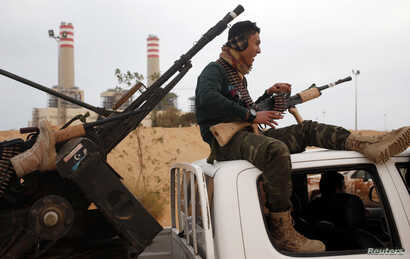 A fighter from Misrata sits on top of a vehicle near Sirte, March 16, 2015.