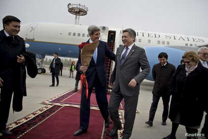 U.S. Secretary of State John Kerry (center L) shares a laugh with Kyrgyz Foreign Minister Erlan Abdyldaev upon his arrival at Manas International Airport in Bishkek, Oct. 31, 2015.