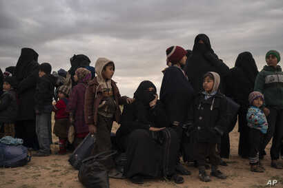 Women and children evacuated out of the last territory held by Islamic State militants wait to be screened by U.S.-backed Syrian Democratic Forces in the desert outside Baghuz, Syria, Feb. 27, 2019.