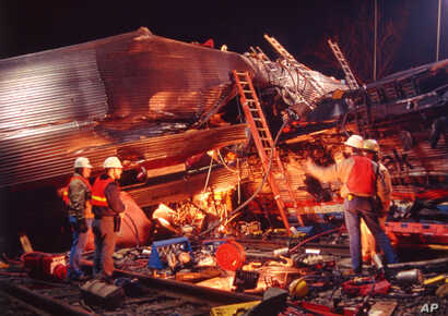 FILE - Workmen survey the damage from the collision between an Amtrak passenger train and three Conrail diesel engines, in Chase Md., Jan 4, 1987. Sixteen people were killed and more than 170 injured in the collision.