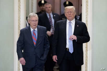 President Donald Trump accompanied by Senate Majority Leader Mitch McConnell of Kentucky, left, arrives for a Senate Republican Policy lunch on Capitol Hill in Washington, May 15, 2018.