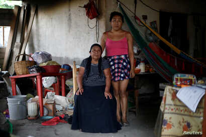 Ximena, 26, an indigenous Zapotec transgender woman, poses for a photo next her mother inside her house destroyed after an earthquake Sept. 10, 2017.