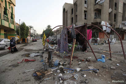 A woman walks past the site of a car bomb attack at Palestine Street in Baghdad, Nov. 2, 2014.