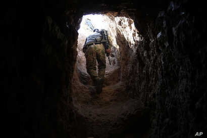 A peshmerga fighter walks through a tunnel made by Islamic State fighters, Oct. 18, 2016. The fighters built tunnels under residential areas so they could move without being seen from above to avoid airstrikes.