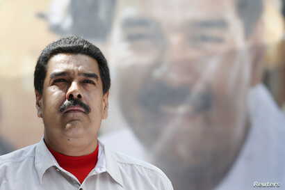 Venezuela's President Nicolas Maduro stands in front of a picture of himself during a meeting with government workers in Caracas, Nov. 20, 2015.