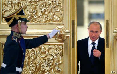Russian President Vladimir Putin, right, enters the Alexadrovsky Hall to head a meeting of the Presidential Council for Civil Society and Human Rights  at the Kremlin in Moscow, Russia, Thursday, Oct. 1, 2015.