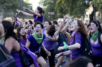 FILE - Women participate in a demonstration to commemorate International Women's Day in Buenos Aires, Argentina.