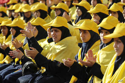 FILE - Hezbollah supporters applaud as they listen to Hezbollah leader Sayyed Hassan Nasrallah on a televised speech on giant screens during an election campaign in a southern suburb of Beirut, Lebanon, April 13, 2018. Nasrallah said a recent attack ...