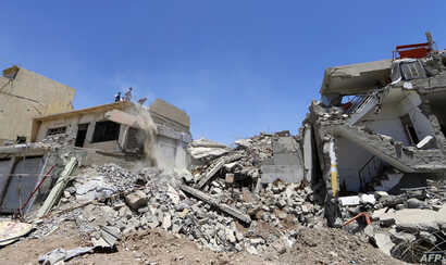 Iraqis clear the debris of a building in west Mosul on June 3, 2017, after it was retaken by government forces during their ongoing battle against Islamic State (IS) group fighters.