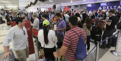 Passengers wait in line at the Delta airlines counter in terminal 2 at the Fort Lauderdale-Hollywood International Airport in Fort Lauderdale, Fla., Jan. 7, 2017.