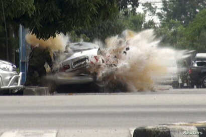 FILE - A car bomb explodes as a member of a Thai bomb squad checks it in Narathiwat province, south of Bangkok July 1, 2011. The bomb planted by suspected insurgents wounded the squad member, police said.