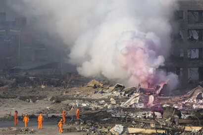 Fire fighters in protective gear watch partially pink smoke continue to billow after an explosion at a warehouse in northeastern China's Tianjin municipality, Aug. 13, 2015.