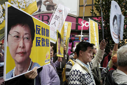 Protesters raise placards and banner during a rally against Hong Kong's former Chief Secretary Carrie Lam in Hong Kong,  Feb. 5, 2017.