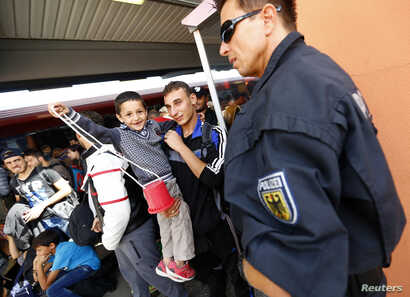 A child plays as migrants are taken out of trains by the police near the border with Austria in Freilassing, Germany, Sept. 15, 2015.
