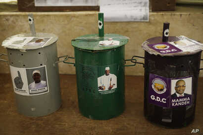 Three ballot drums are set in a polling station in Serrekunda, Gambia, Wednesday Nov. 30, 2016. Voters will choose their candidate by placing a marble inside the drum of their choice.