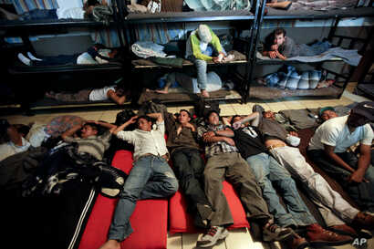 FILE - In this April 28, 2010, file photo, men look for a place to sleep in a crowded shelter for migrants deported from the United States, in the border city of Nogales, Mexico.