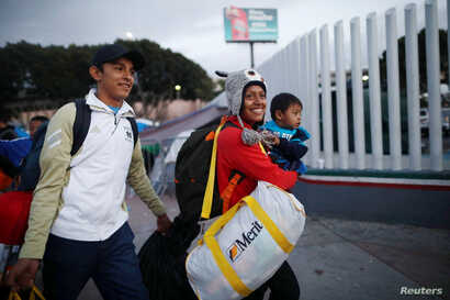A family, members of a caravan of migrants from Central America, enter the United States border and customs facility, where they are expected to apply for asylum, in Tijuana, Mexico, May 2, 2018.