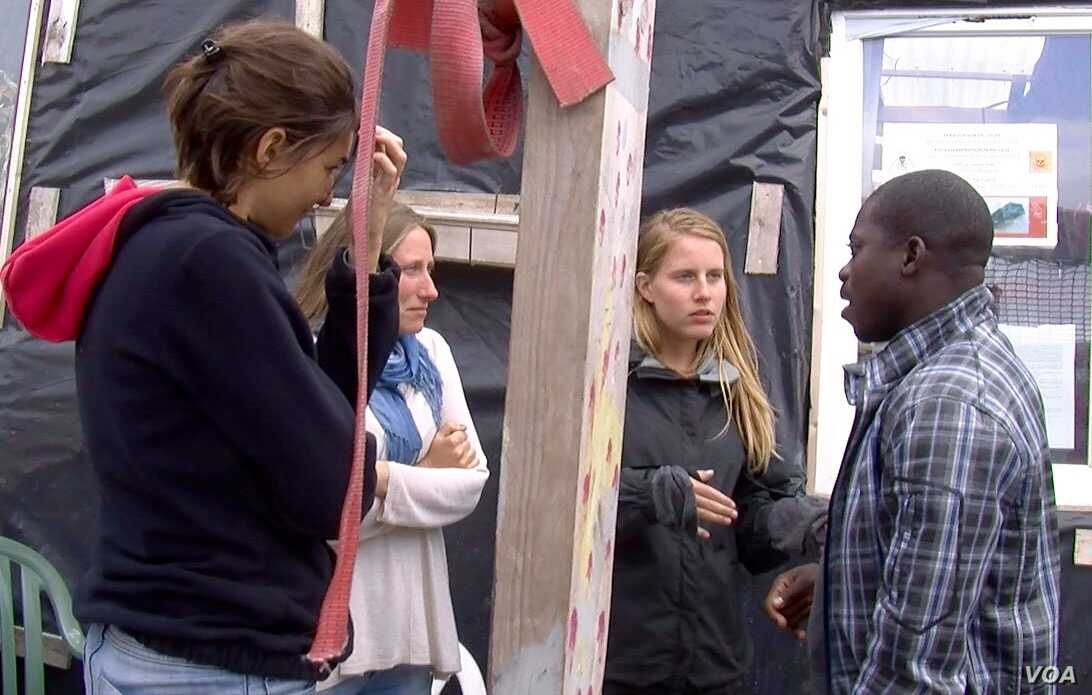 Nigerian Zimako Jones (R), who founded a migrant school at the Jungle camp, talks with volunteer teachers. (L. Bryant/VOA)