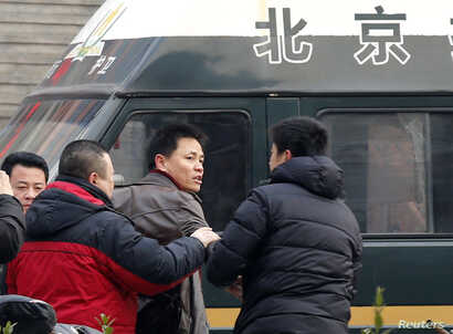 Zhang Xuezhong (C), a lawyer for Chinese dissident Zhao Changqing, argues with plain-clothed policemen as he refuses to show them his identification card when he was stopped and questioned by them on his way to court to attend Zhao's trial in Beijing...
