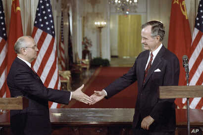 Soviet President Mikhail Gorbachev, left, and President George H. Bush shake hands following the signing of accords at the White House in Washington on Friday, June 1, 1990.