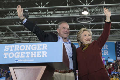 Democratic presidential nominee Hillary Clinton and her running mate, Virginia Sen. Tim Kaine, wave at supporters during a campaign event at Taylor Allderdice High School in Pittsburgh, Pa., Oct. 22, 2016.