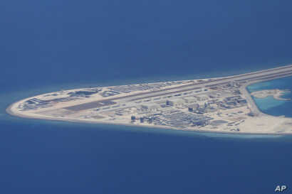 FILE - an airstrip, structures and buildings on China's man-made Subi Reef in the Spratly chain of islands in the South China Sea are seen from a Philippine Air Force C-130 transport plane of the Philippine Air Force.