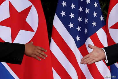 FILE - U.S. President Donald Trump and North Korea's leader Kim Jong Un reach to shake hands at the start of their summit at the Capella Hotel on the resort island of Sentosa, Singapore, June 12, 2018.