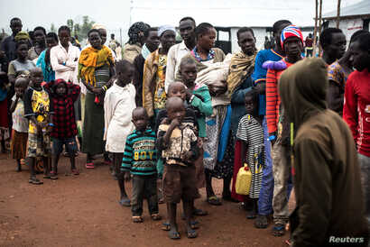 South Sudanese people wait at a transit centre in Koluba before boarding courtesy buses to Imvepi refugee settlement camp in Arua District, northern Uganda, Aug. 12, 2017.