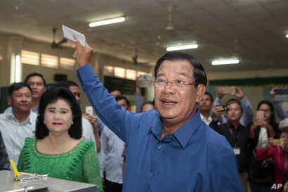 Prime Minister Hun Sen of the Cambodian People's Party shows off his ballot paper before voting in local elections at Takhmau polling station in Kandal province, southeast of Phnom Penh, June 4, 2017.