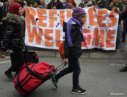 Migrants are welcomed as they arrive at the main railway station in Dortmund, Germany, Sept. 6, 2015.