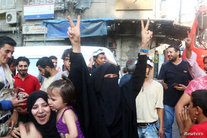 A woman flashes the victory sign as she celebrates the news of the breaking of the siege of rebel-held areas of Aleppo, Aug. 6, 2016.